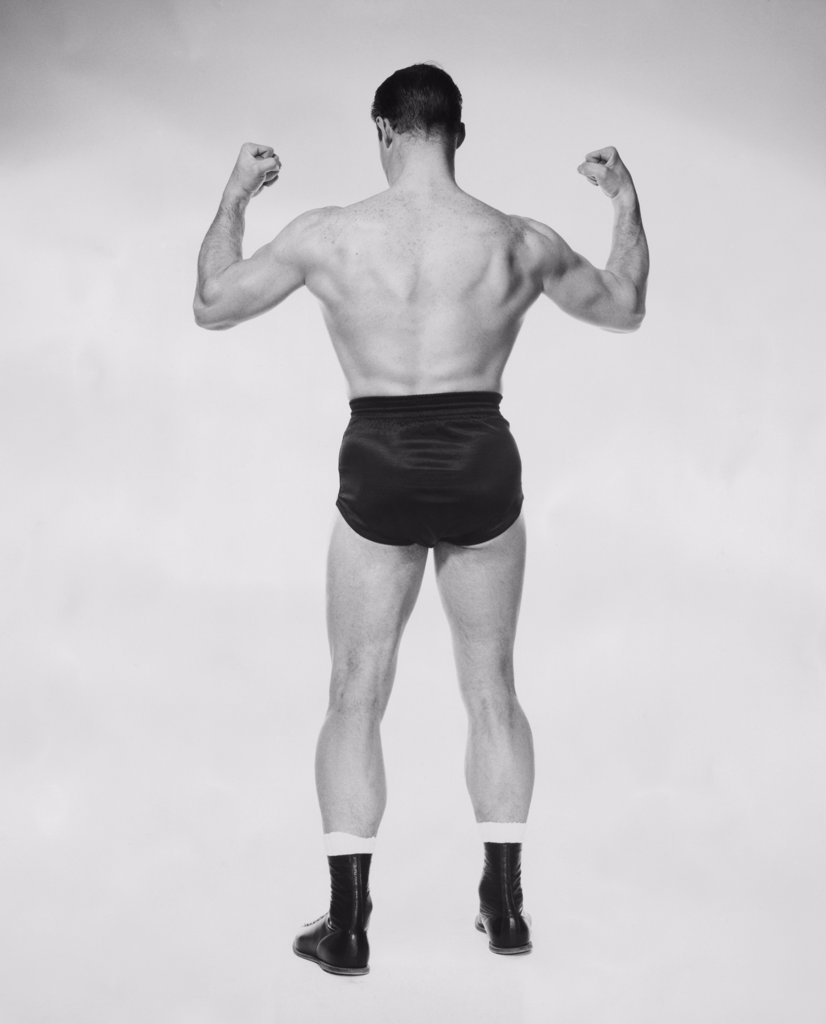 Stock Photo: 255-24325 Rear view of a male body builder flexing his muscles