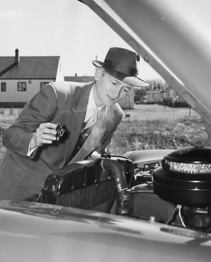 Stock Photo: 255-24886 Mature man examining the engine of his car