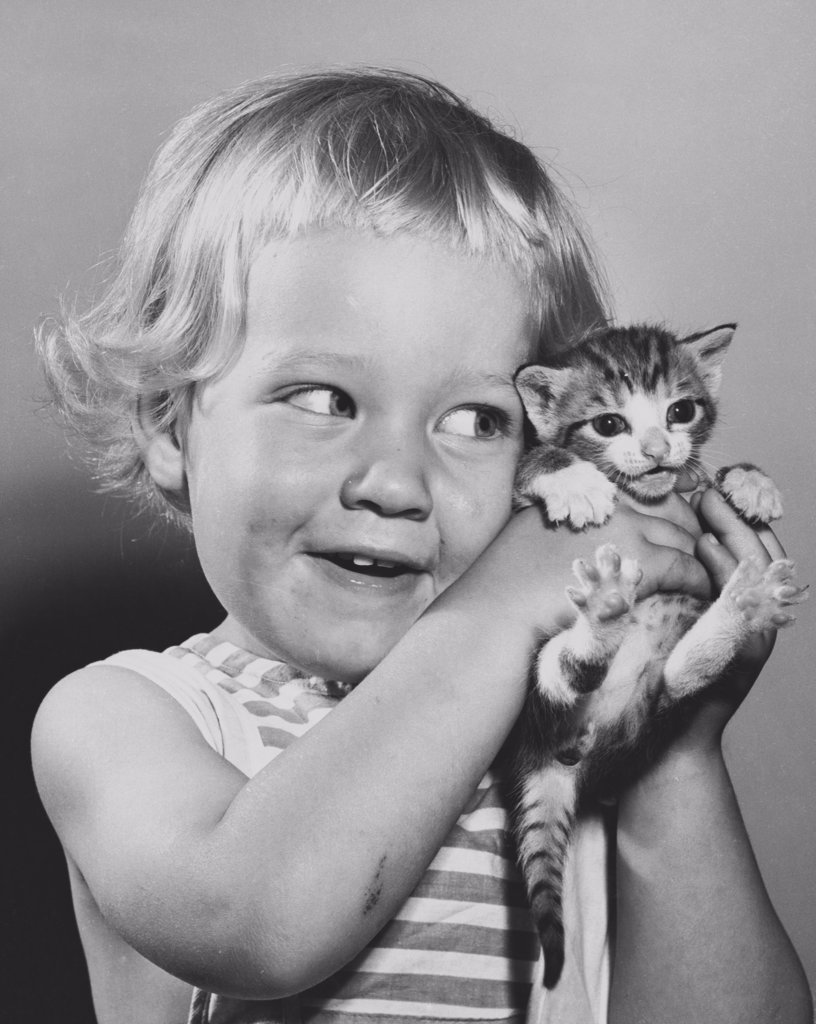 Close-up of a girl smiling and cuddling a kitten : Stock Photo