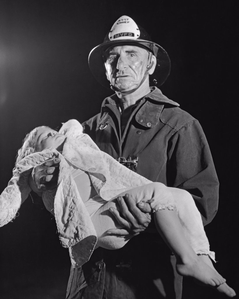 Portrait of a fireman carrying an injured child : Stock Photo