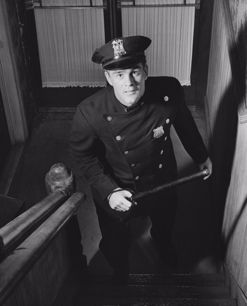Stock Photo: 255-26100 High angle view of a policeman walking up staircase