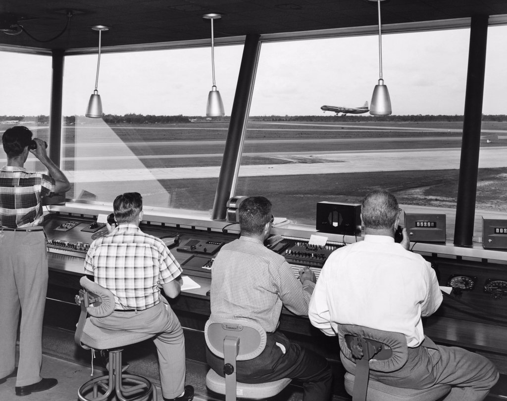 Stock Photo: 255-26592A Rear view of four technicians working in an air traffic control tower, Sarasota-Bradenton International Airport, Sarasota, Florida, USA
