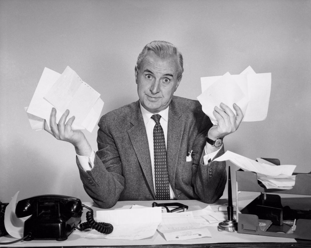 Stock Photo: 255-2740 Businessman sitting at a desk and holding documents