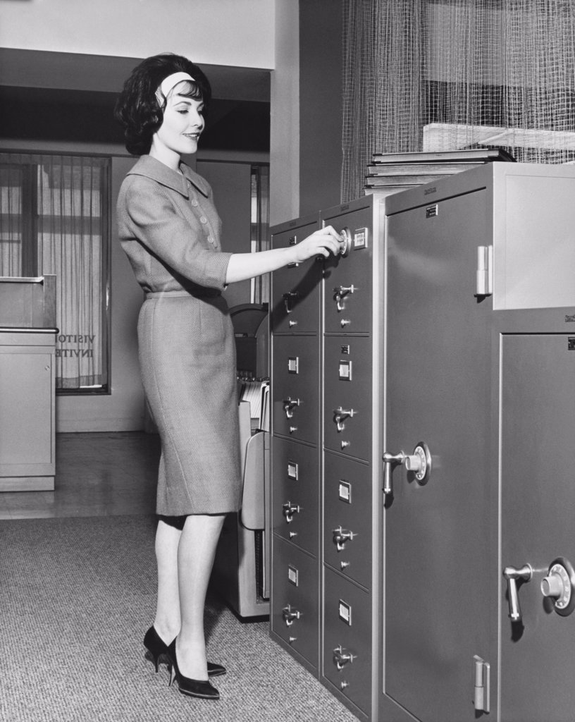 Businesswoman opening a filing cabinet : Stock Photo