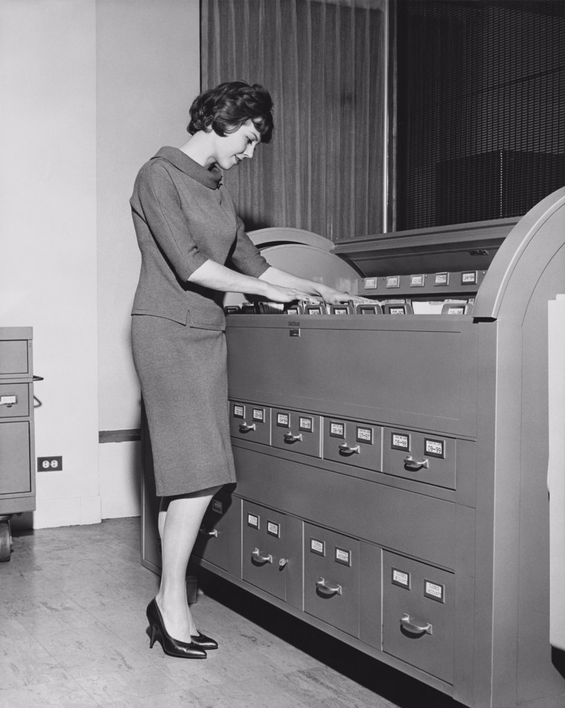 Stock Photo: 255-28025 Side profile of a businesswoman searching for files in a filing cabinet