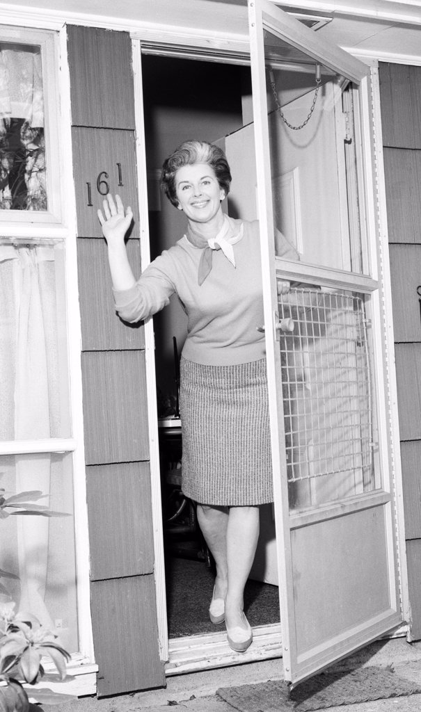 Woman in doorway waving to camera : Stock Photo