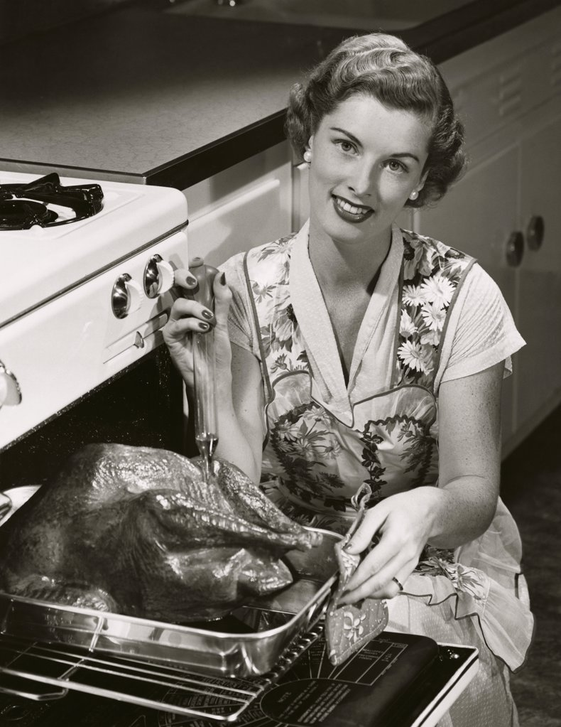 Portrait of a young woman putting a turkey into an oven : Stock Photo