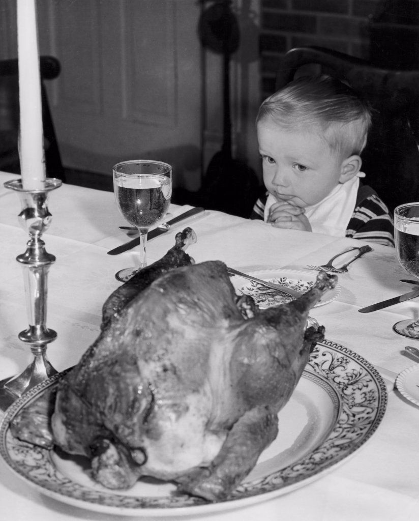 High angle view of a boy sitting at a dining table and looking at a roasted turkey on Thanksgiving day : Stock Photo