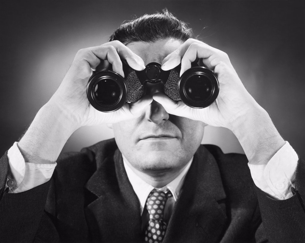 Close-up of a man looking through binoculars : Stock Photo