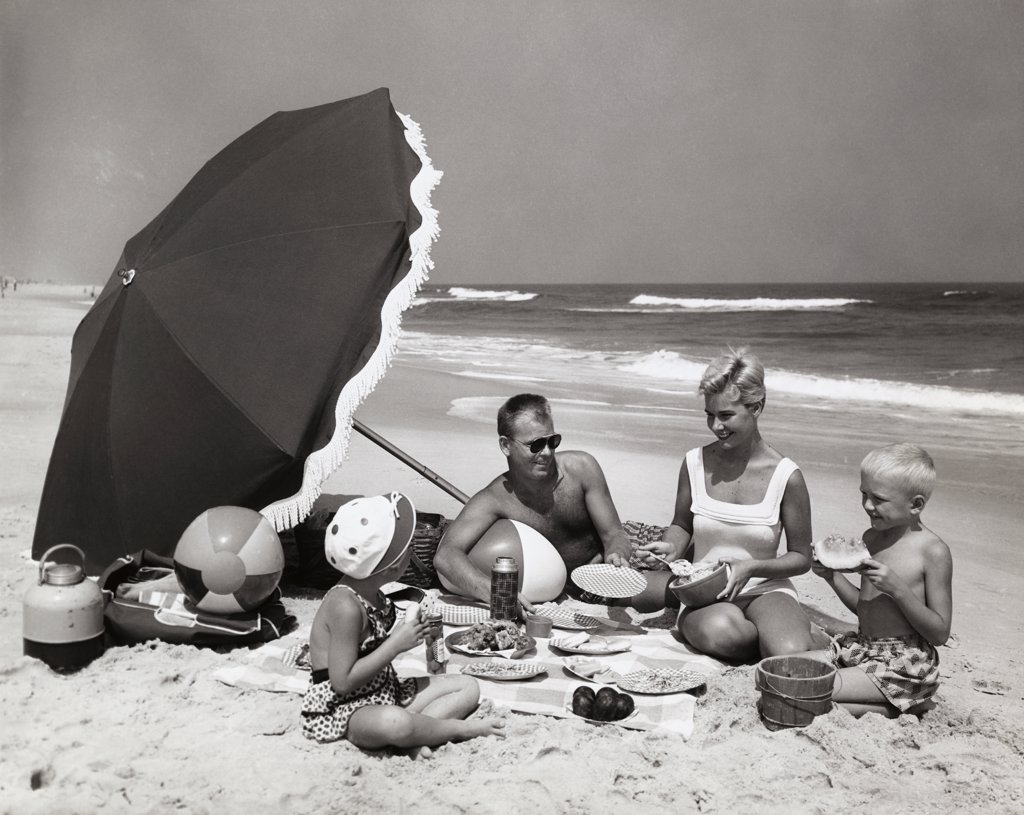 Stock Photo: 255-3142 Parents and their two children having a picnic on the beach