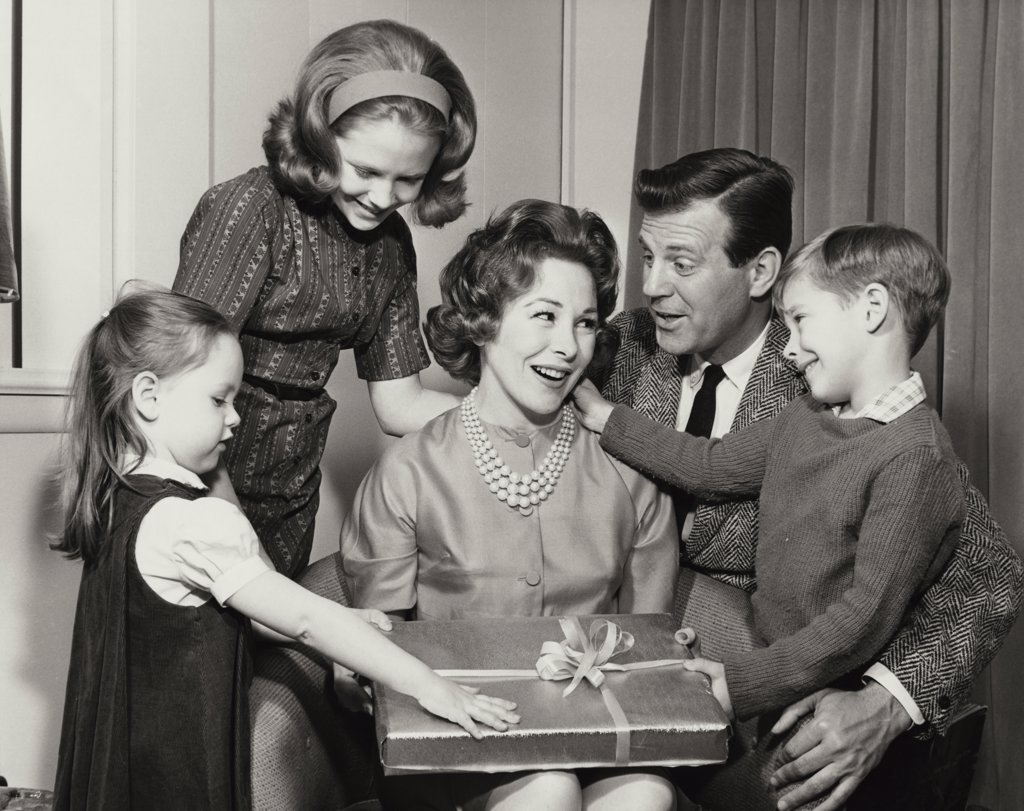 Close-up of a mature woman holding a birthday present with her family beside her : Stock Photo