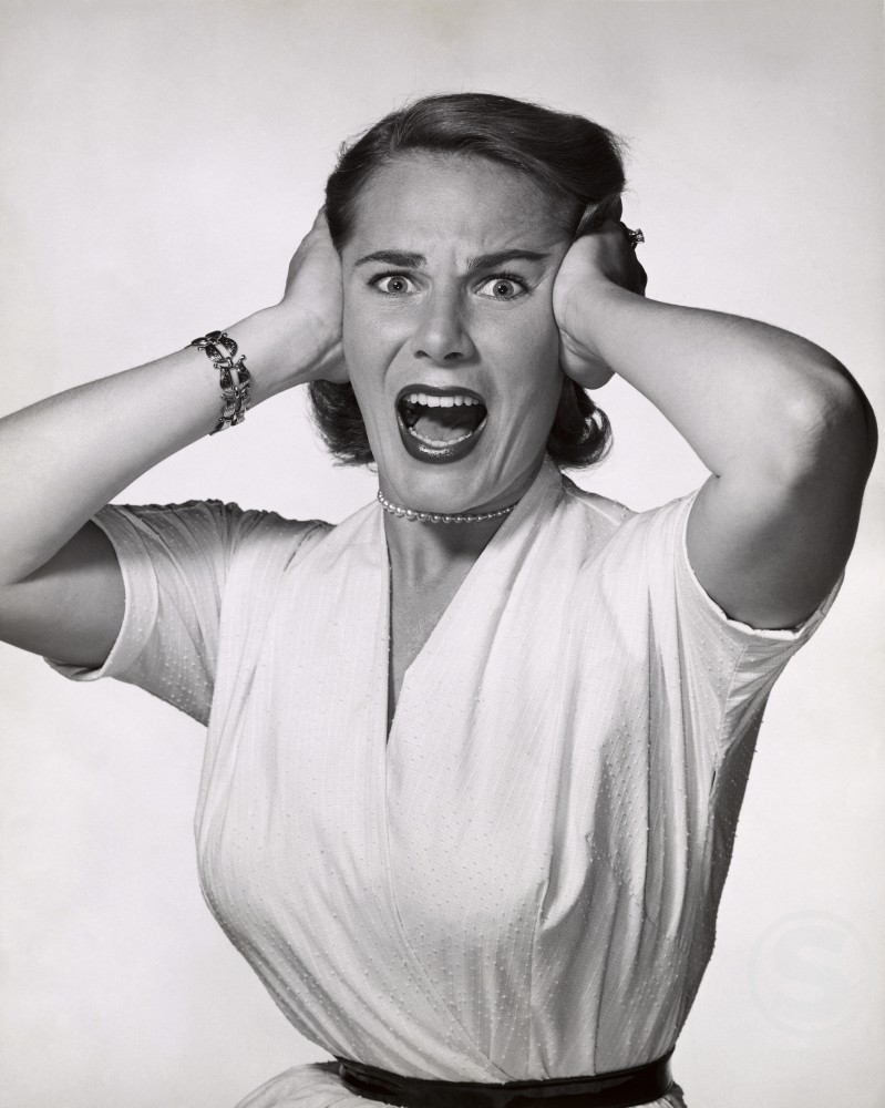 Portrait of a young woman holding her head screaming : Stock Photo