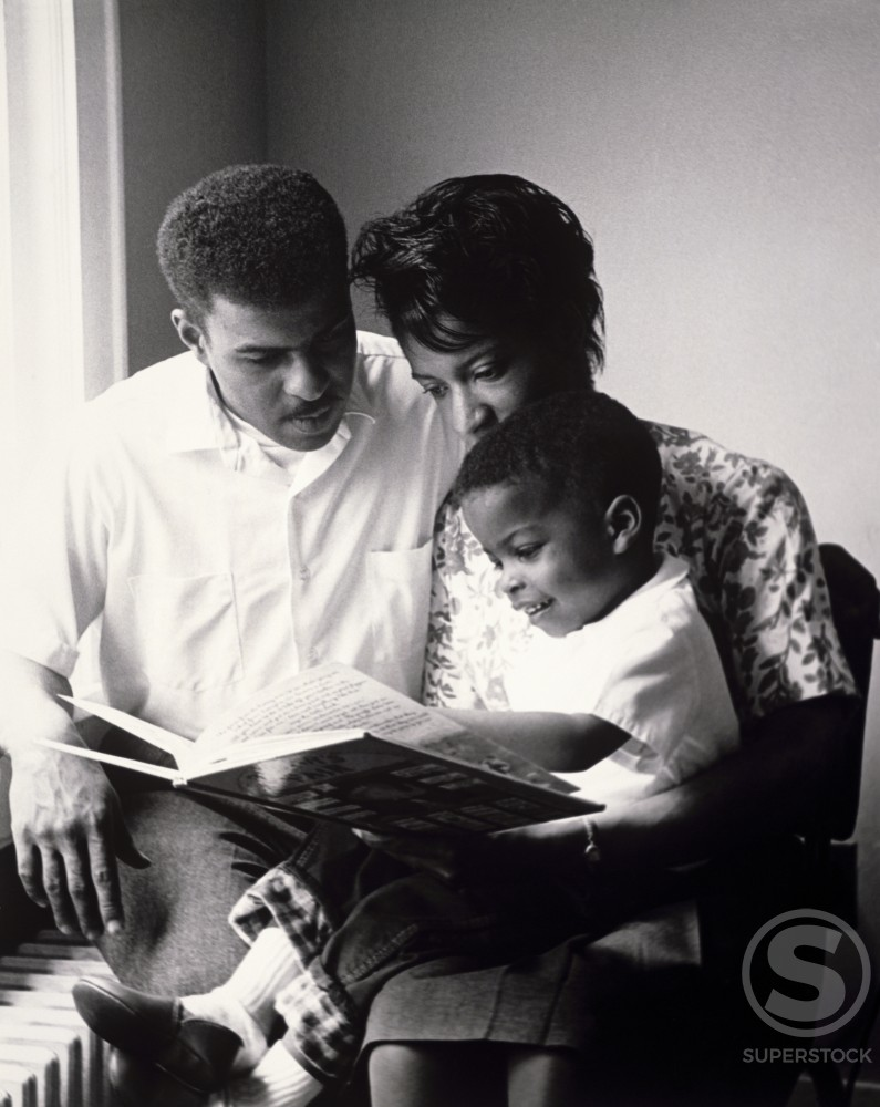 Parents reading to their son : Stock Photo