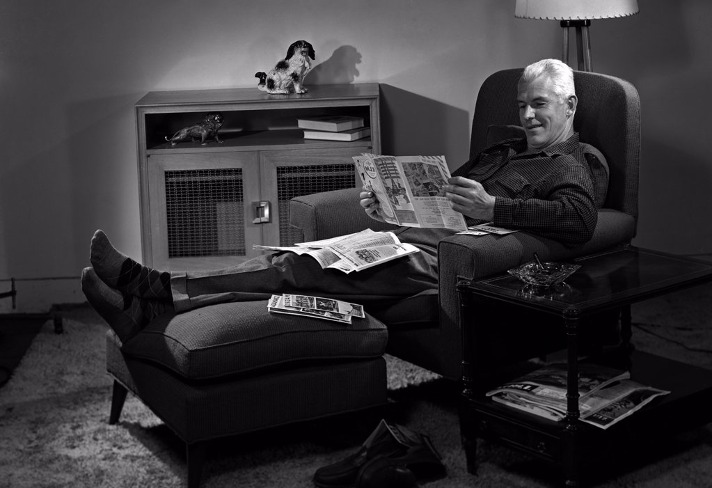 Man relaxing in chair reading newspaper : Stock Photo