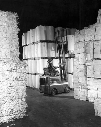 Rear view of a worker driving a forklift in a paper warehouse : Stock Photo