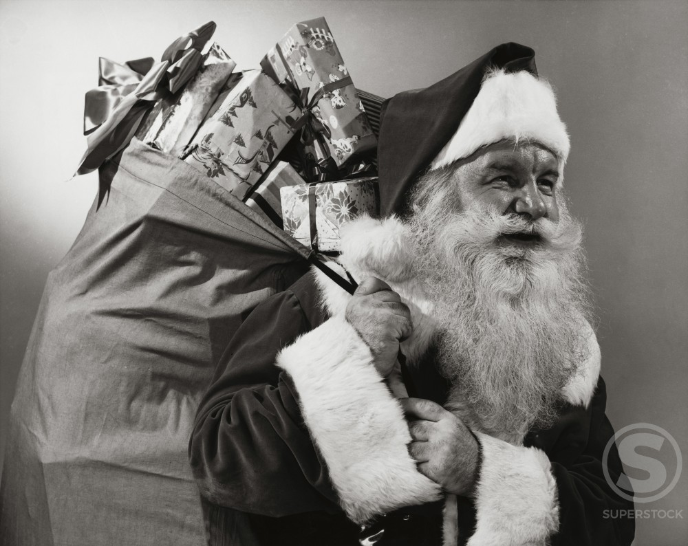 Stock Photo: 255-3522 Side profile of Santa Claus carrying a sack of Christmas presents on his back