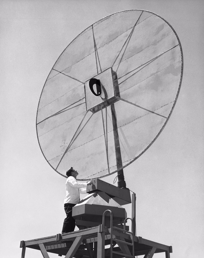Stock Photo: 255-35525 Low angle view of an engineer standing in front of a Scimitar antenna