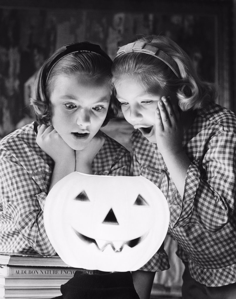 Close-up of two girls looking at an illuminated jack o' lantern : Stock Photo