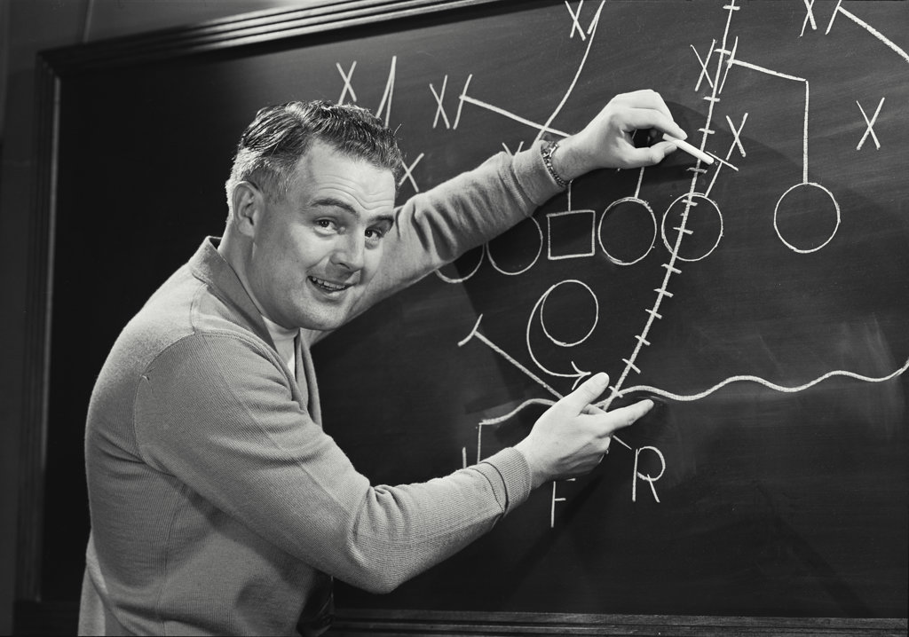 Portrait of a football coach explaining game play on the blackboard : Stock Photo