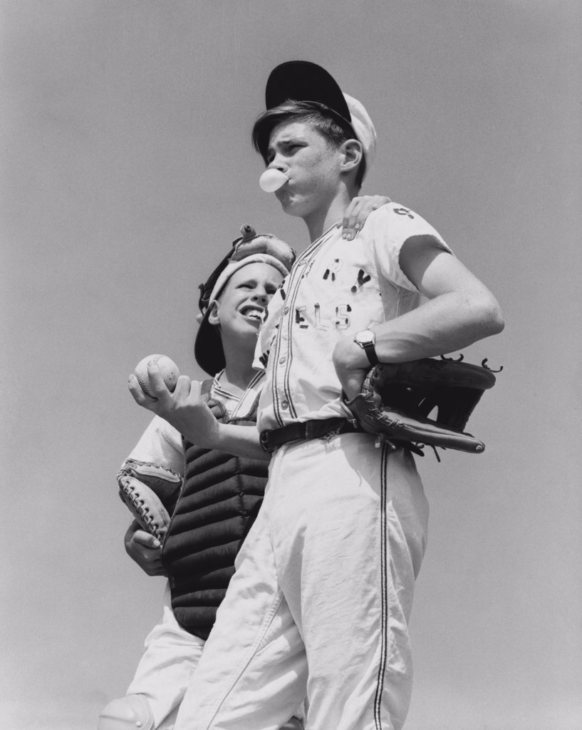 Low angle view of a youth league pitcher standing with a baseball catcher : Stock Photo
