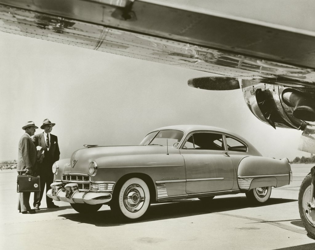 Two businessmen standing near a car, 1949 Cadillac Series 62 Club Coupe : Stock Photo