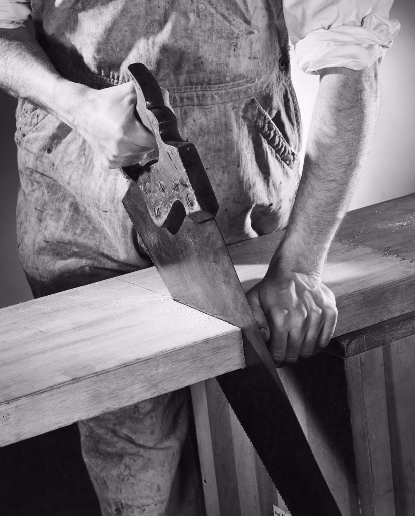 Stock Photo: 255-37076 Mid section view of a carpenter sawing a wooden plank