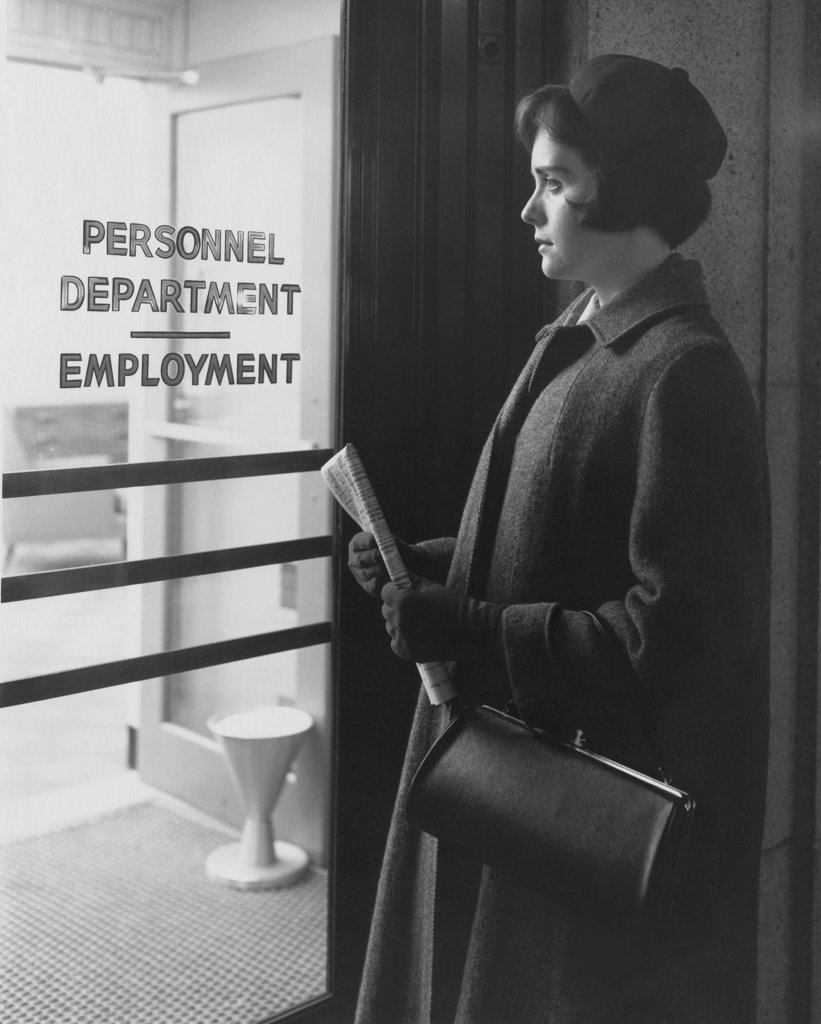 Young woman standing outside an employment office : Stock Photo