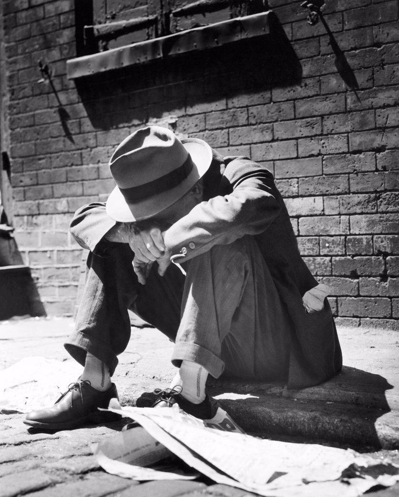 Homeless man sitting on a sidewalk : Stock Photo