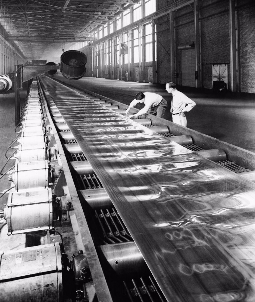 Two people examining the strip of aluminum sheet being processed through large rolling mills : Stock Photo