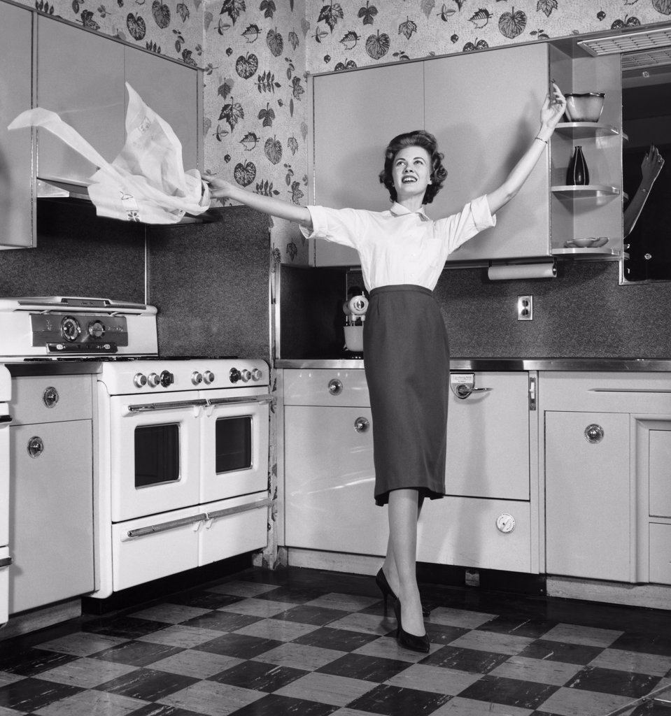 Stock Photo: 255-38367 Young woman in kitchen tossing apron in air