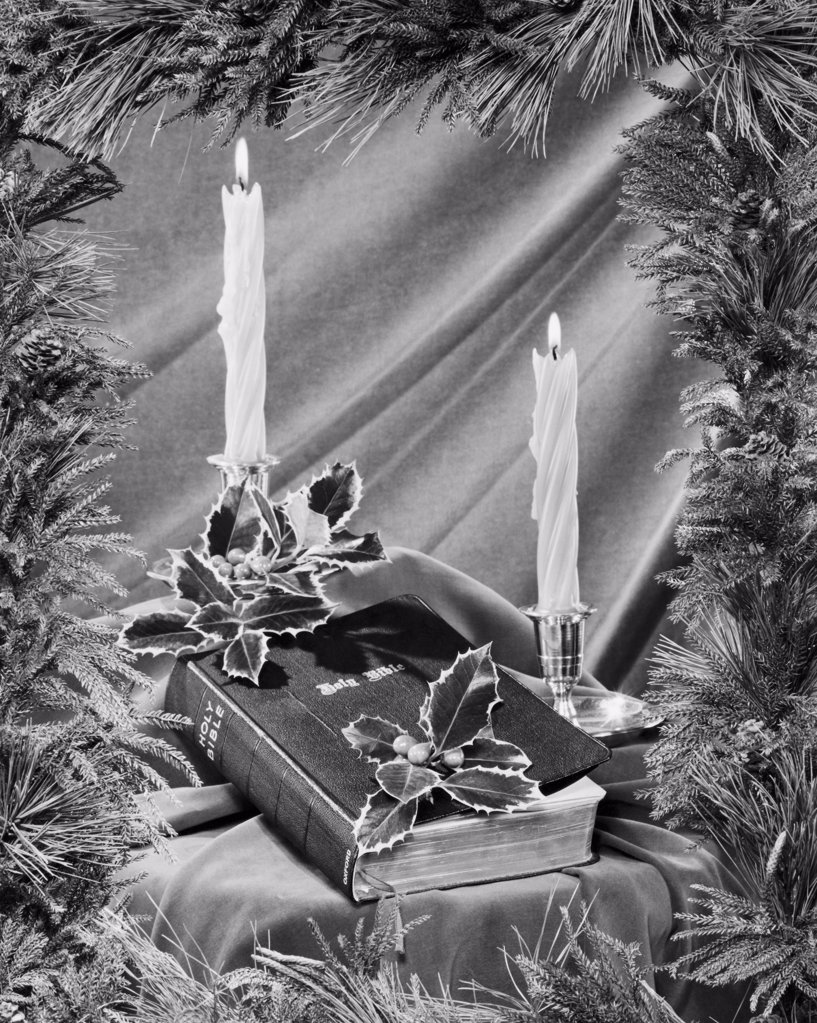 Two candles burning near a Bible : Stock Photo