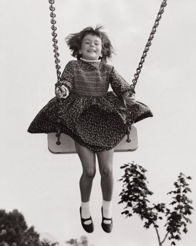 Stock Photo: 255-3972 Low angle view of a girl on a swing