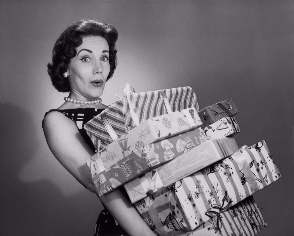 Portrait of a young woman holding a stack of Christmas present : Stock Photo