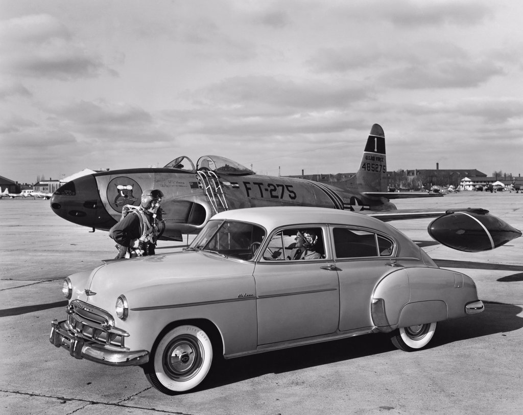 Stock Photo: 255-40132 Vintage car near an airplane on a runway