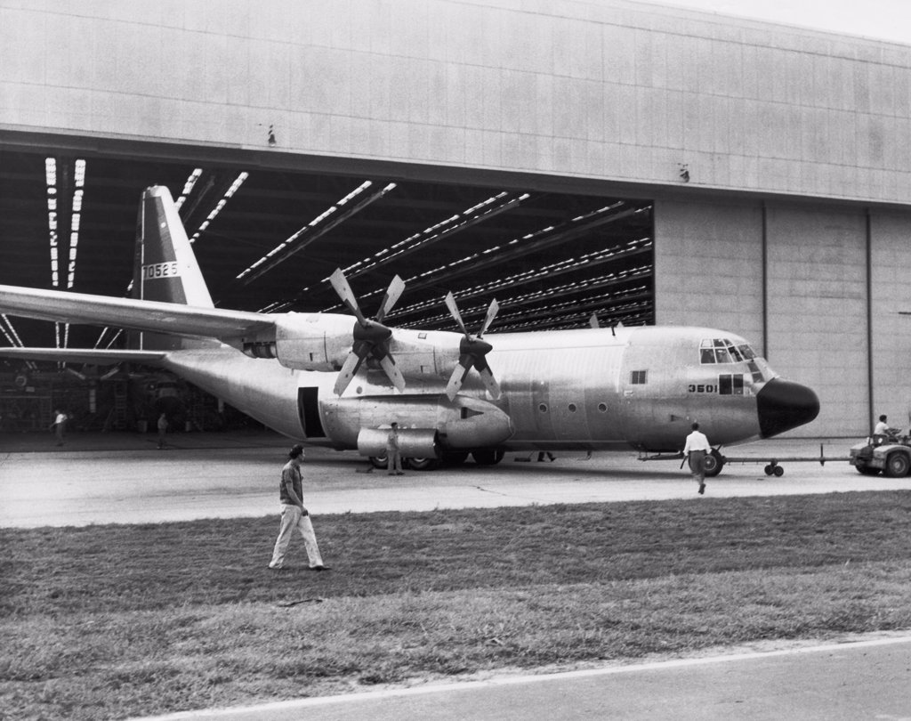 Stock Photo: 255-40503 Land vehicle hauling an airplane out of a hanger, C-130B Hercules