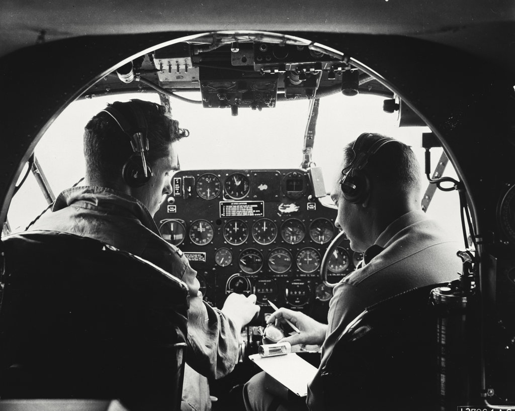 Instructor giving pre-flight instruction to a student in a C-45 airplane : Stock Photo