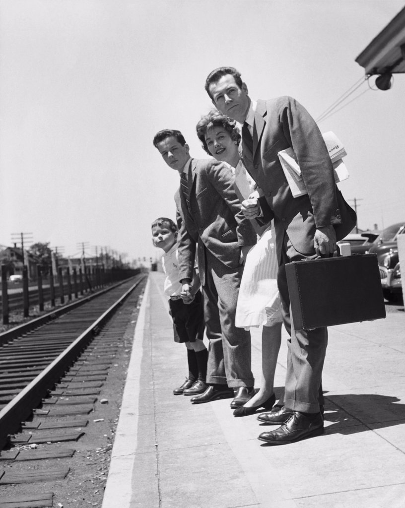 Parents with their children standing on a railroad station platform : Stock Photo