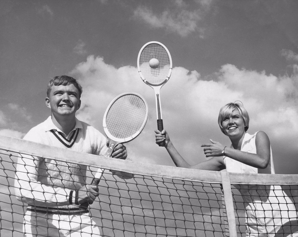Stock Photo: 255-41376 Low angle view of young couple playing tennis