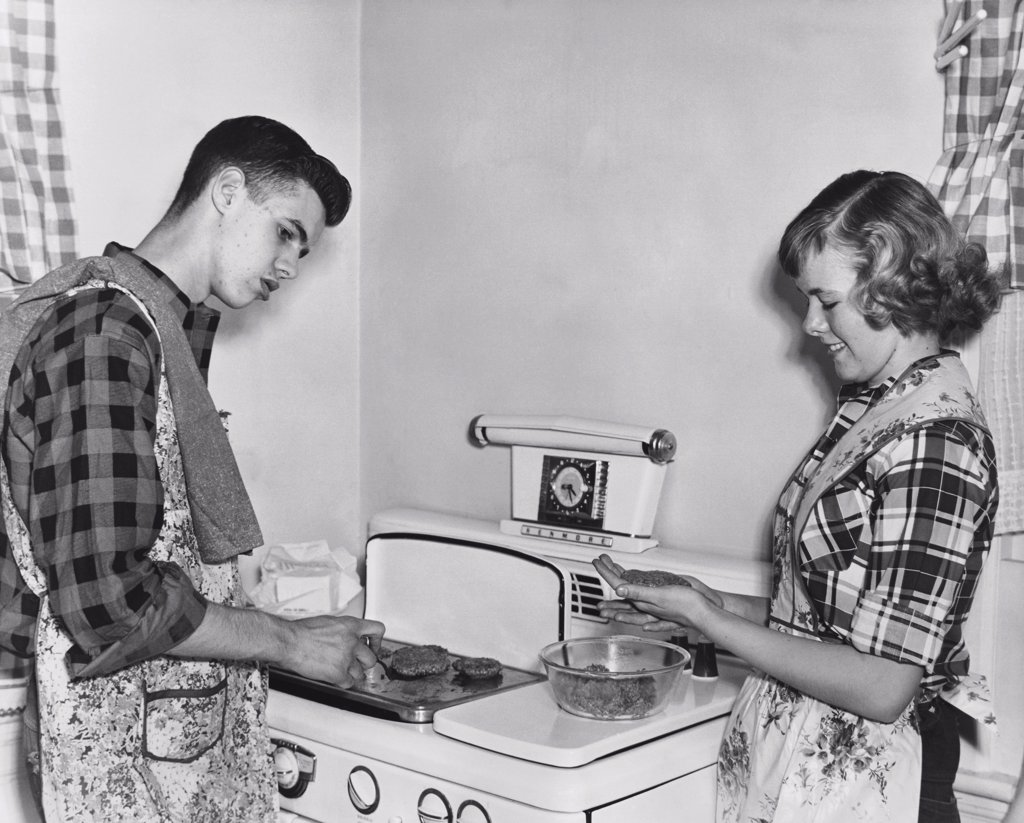 Stock Photo: 255-41389 Teenage couple cooking hamburgers on a stove