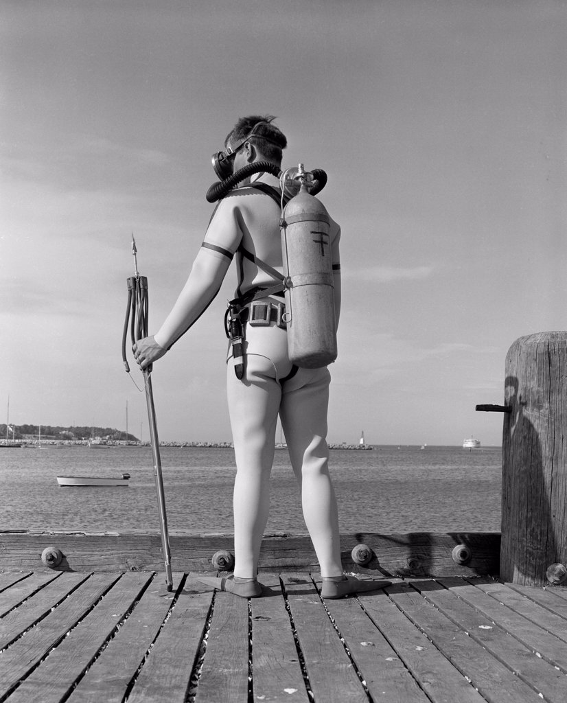 Stock Photo: 255-416339 Man on jetty preparing for underwater diving
