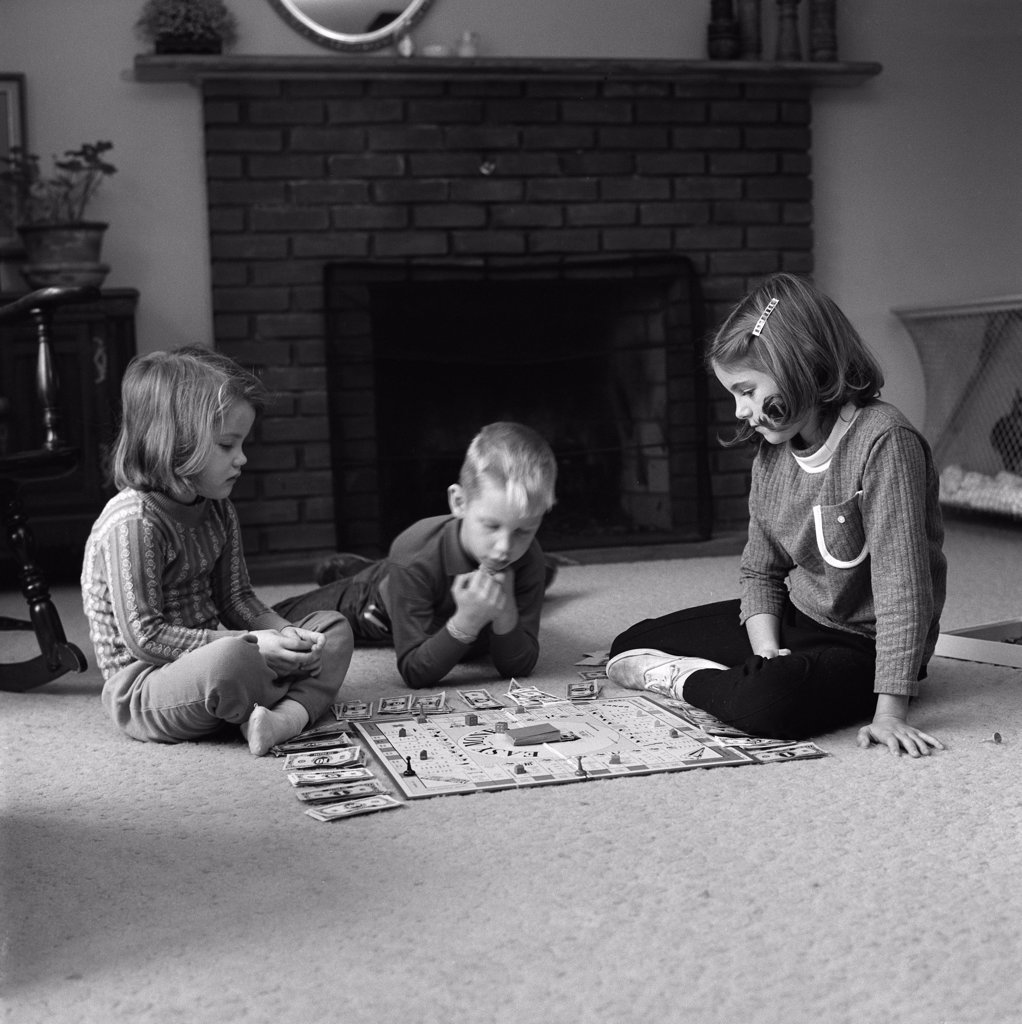 Children  playing board game on carpet : Stock Photo