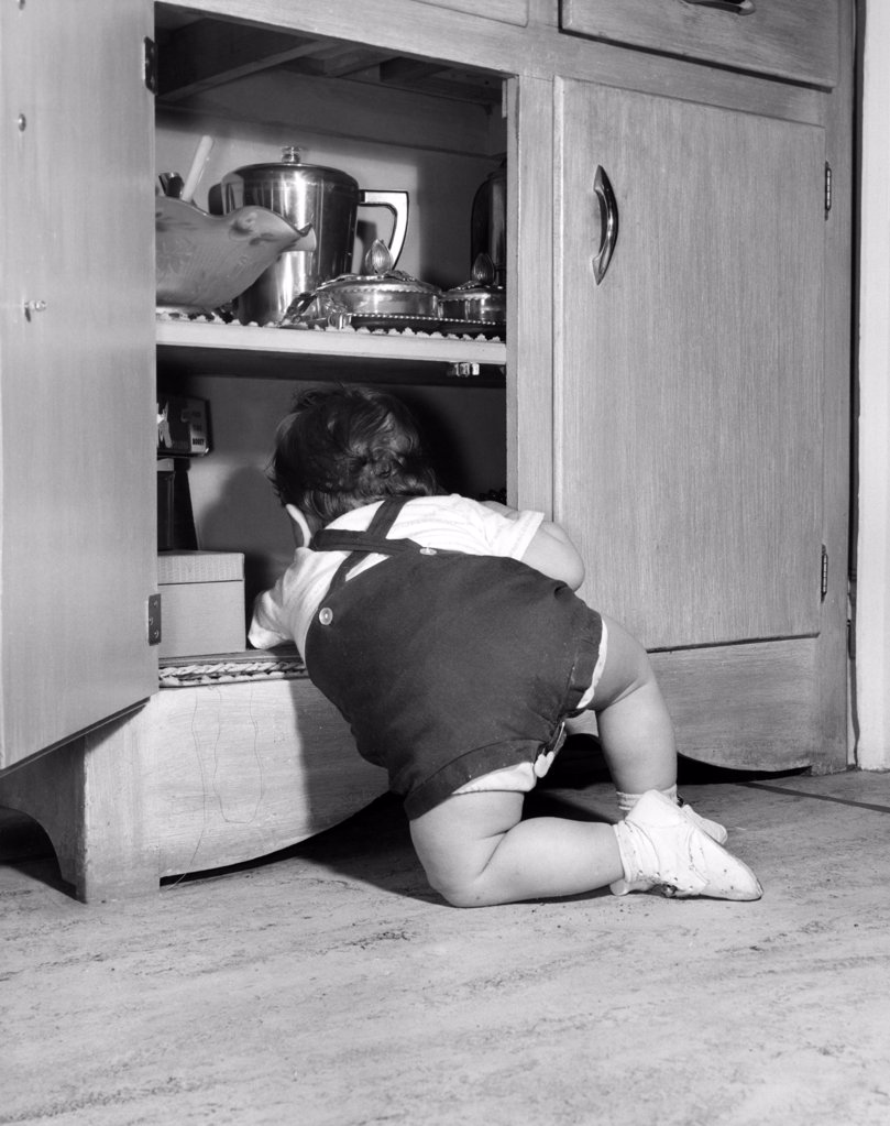 Stock Photo: 255-416571 Baby boy playing in open cupboard, rear view