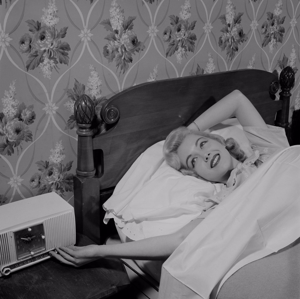 Stock Photo: 255-417025 Young woman lying in bed listening to radio