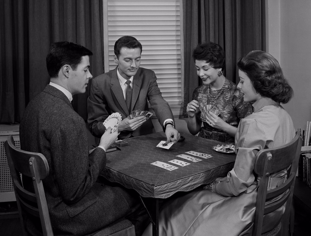 Two couples playing cards indoors : Stock Photo