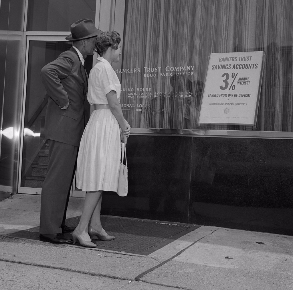 Stock Photo: 255-417130 Mid adult couple examining bank offer, standing outside bank