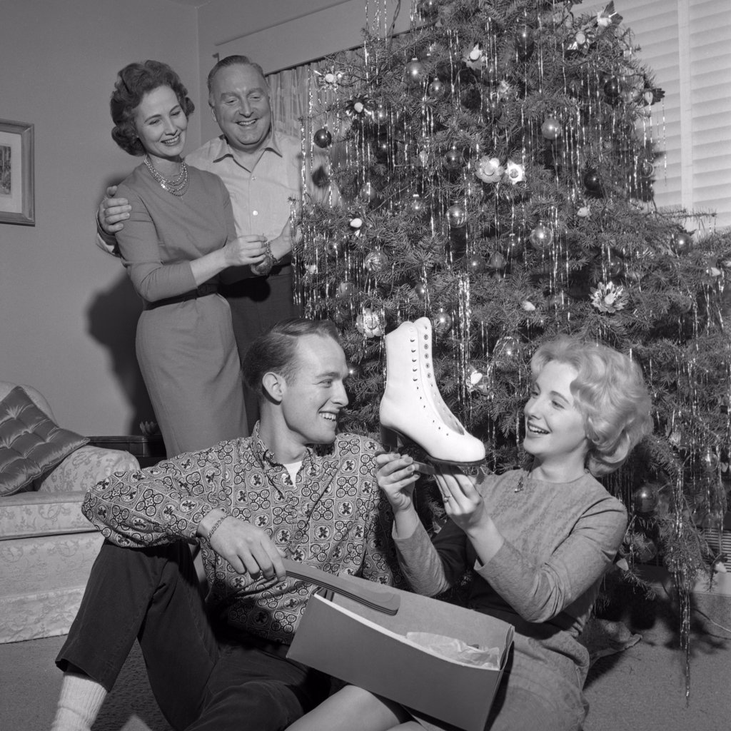 Stock Photo: 255-417350 Young woman holding new ice skate, parents standing near Christmas tree