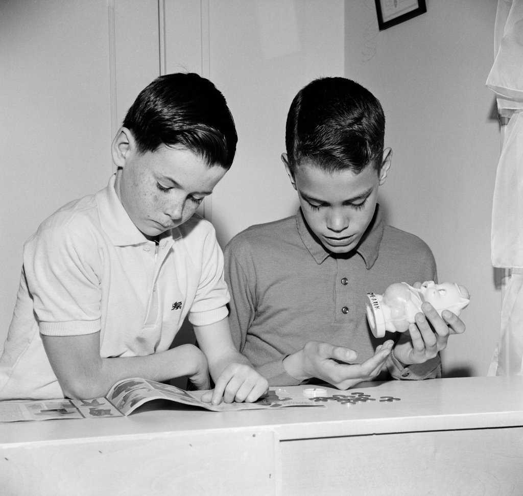 Stock Photo: 255-417780 Two boys reading magazine and taking out money from money-box