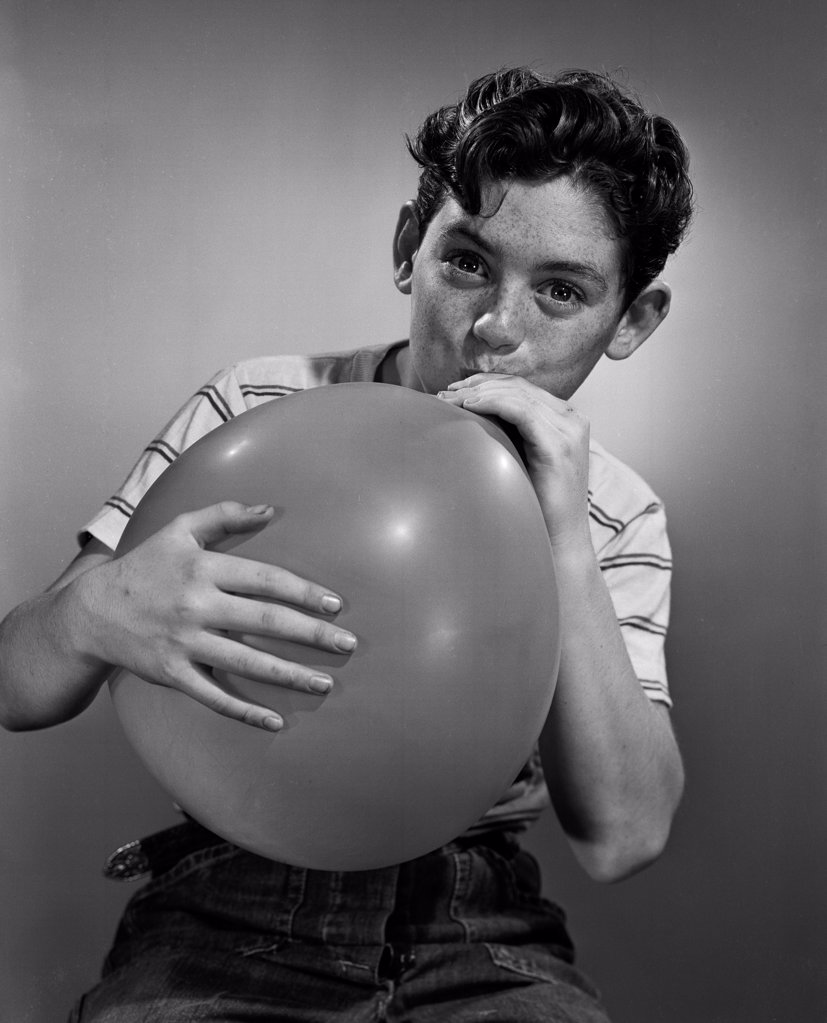 Stock Photo: 255-417935 Boy blowing balloon