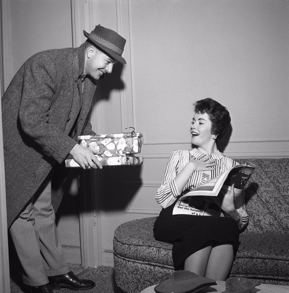 Stock Photo: 255-418055 Young woman receiving presents from young man