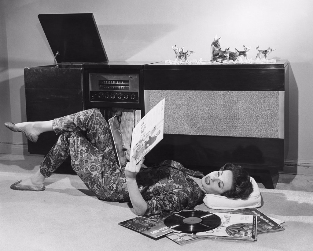Stock Photo: 255-41808 Side profile of a young woman lying on the floor holding records